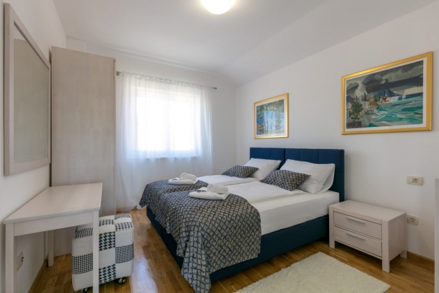 Double bedded modern room decorated with amazing wall paintings in the Villa Makarac